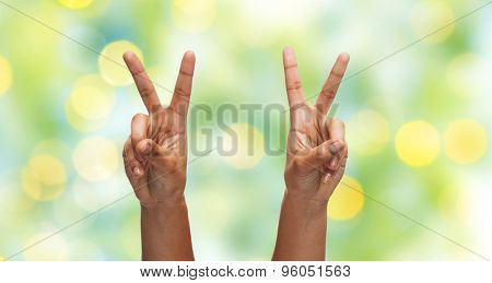 gesture, people and body parts concept - african woman two hands showing victory or peace over blue sky and clouds background