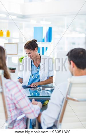 Rear view of pregnant woman and her husband discussing with doctor in an examination room