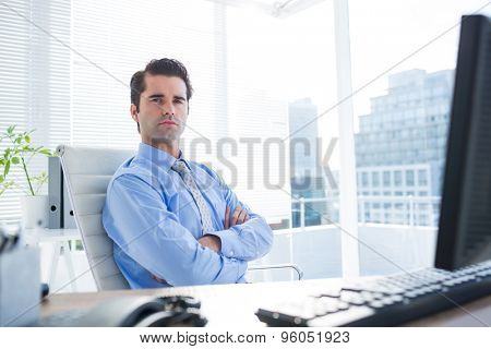 Serious businessman crosses his arms on his office