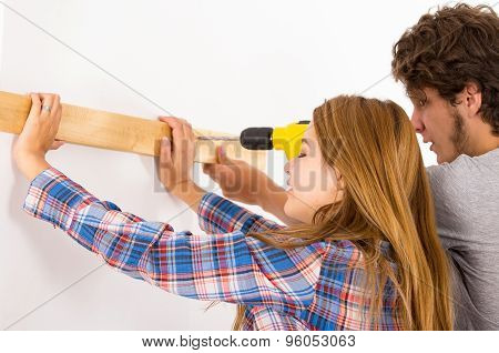 Couple renovating together as man using power drill on wooden plank being held up by woman