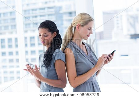 Back to back businesswomen texting messages in the office