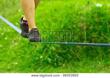Closeup womans feet with shoes balancing on slackline and grassy background