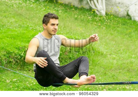 Man sitting on slackline left arm to the side concentrating keeping balance with grassy background
