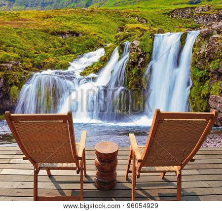 Deck chairs on a wooden platform waiting for tourists.  Threaded full-flowing waterfall Kirkyufell Foss on the grassy mountains