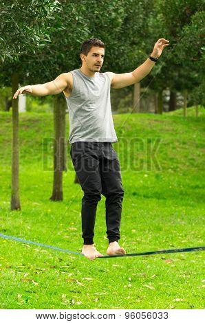 Man walking on slackline in park with arms out maintaining balance and concentrated