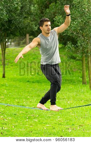 Man walking barefoot on slackline in park with arms out and deep concentrated facial expression