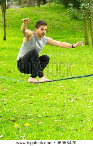 Man sitting with bended knees on slackline in park environment
