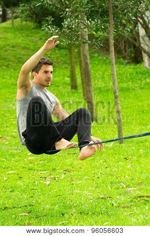 Man sitting on tightrope in park environment