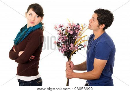 Hispanic couple fighting as man attempts to give girlfriend flowers but she gives him cold shoulder