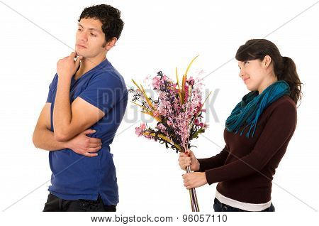 Woman holding flowers up behind mans back with hopeful expression and man expressing dismissive atti