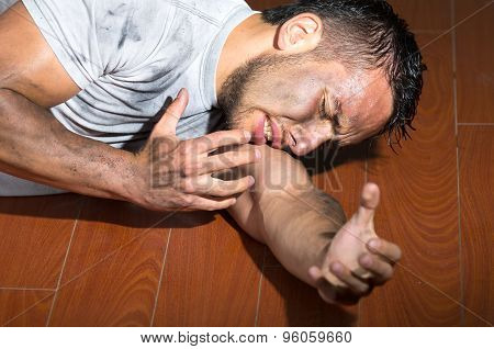 Hispanic man with dirty face and shirt lying on floor left arm reaching towards camera
