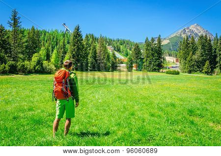 Man with orange backpack and mountain peaks
