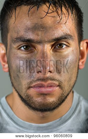 closeup hispanic man with dirty face lookind straight into camera