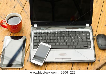 Wooden table with open laptop, mobile, tablet and red coffee mug