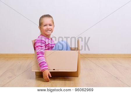 Little curious girl in cardboard box