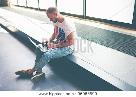 Handsome male freelancer busy working on laptop computer  while typing text on keyboard