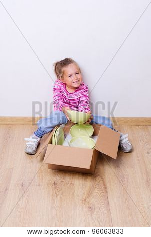 Little smiling girl with dishware