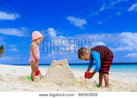 little boy and girl building sandcastle on summer beach