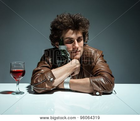 Young Man Is Hugging A Bottle Of Wine / Photo Of Youth Addicted To Alcohol, Alcoholism Concept