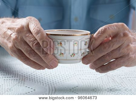 Senior Man Holding Cup Of Tea In Their Hands At Table Close-up