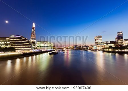 London skyline panorama at night, England the UK in lights. Moon shining. Tower of London, The Shard, City Hall, River Thames. Seen from Tower Bridge