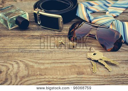 Men accessories: sunglasses, tie, cufflinks, strap, keys, perfume on the old wood background.