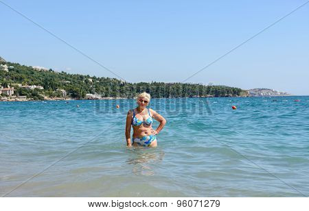 Aged Woman Is Standing In Water Of Sutomore Beach, Montenegro.