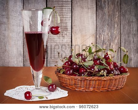 Natural Cherries Drink In The Glass With Fresh Cherry In The Basket On Wooden Table