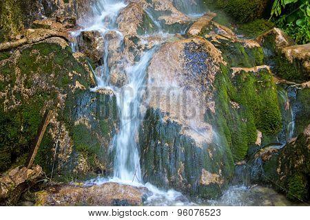 Photo of waterfall in green rocks