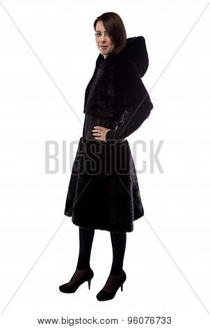 Young woman in fur coat with hands on hips