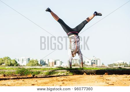 Young fit woman doing simple acrobatics exercise routine in autumn park with city at background