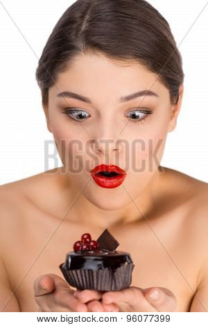 Surprised woman with glossy red lips holding chocolate cake
