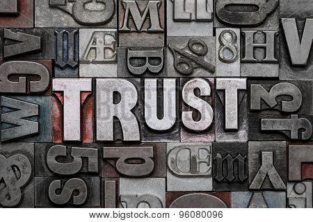The word TRUST in old metal letterpress