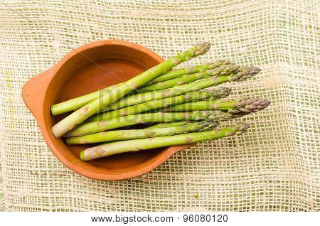 Fresh bunch of green asparagus in ceramic terracota bowl on a hemp cloth