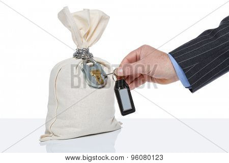 Businessman unlocking a money sack, white background, blank tag on key fob.