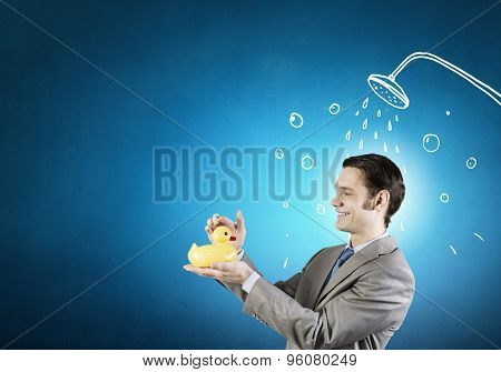 Funny businessman with yellow rubber duck toy