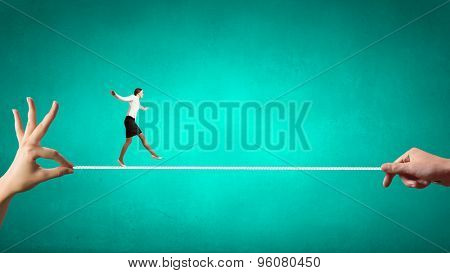 Young brave ricky businesswoman balancing on rope