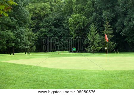 Red flag on a golf course, focus on the flag
