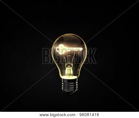 Light bulb with key inside on dark background