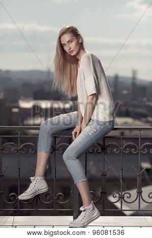 Fashion model. Summer look. Jeans, sneakers, sweater.