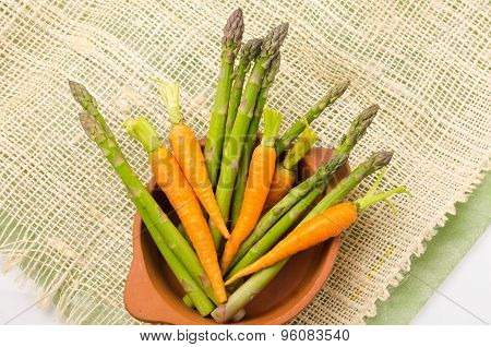 Fresh bunch of green asparagus and carrots  in ceramic terracota bowl on a hemp cloth