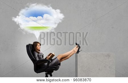Young businesswoman sitting in chair with book in hands