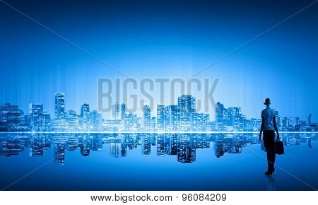 Businesswoman standing with back against night city panoramic view