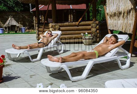 young boys taking a break from swimming and resting on a chaise lounge