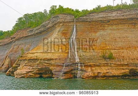 Colorful Falls On A Lakeshore Cliff