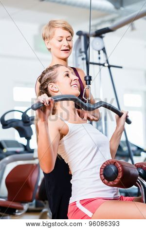 Woman doing back training with trainer in gym at machine