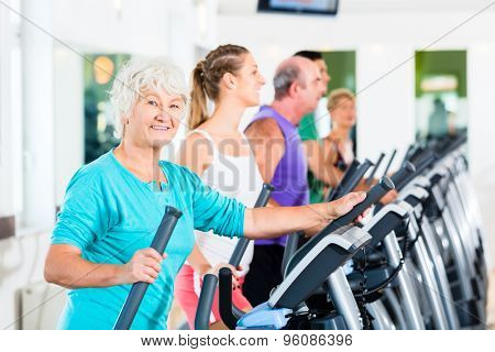 Group with young and Senior women and men on elliptical trainer exercising in gym