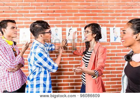 Advertising people choosing key visual among pictures of model hanging from wall