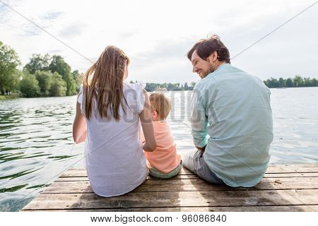 Family sitting on jetty of pond or lake in summer