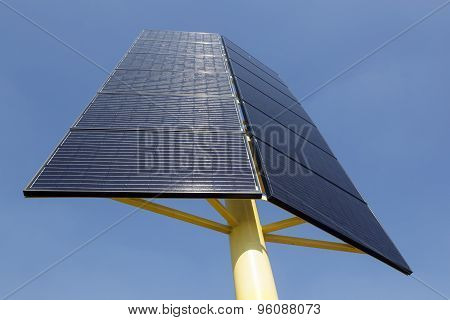 Solar Panels On Yellow Metal Stand And Blue Sky